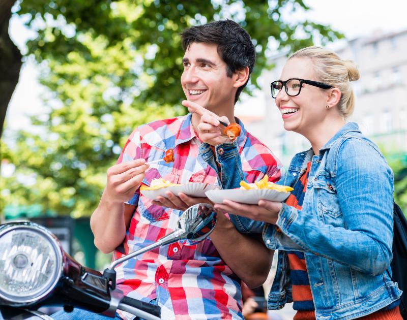 Zwei Person mit Currywurst und Pommes in Berlin